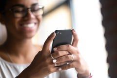 Sluit omhoog handen van jonge smartphone van de zwarteholding royalty-vrije stock foto