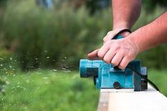 Sluit omhoog handen van timmerman die met elektrische planer aan houten plank werkt stock foto