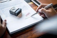 Sluit omhoog handen van zakenman het ondertekenen en zegel op document document om de overeenkomst van het handelsinvesteringenco stock foto's