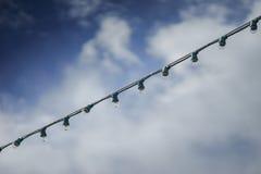 Sluit omhoog hangende gloeilampen met blauwe hemel en betrek op achtergrond, waterdaling op een bol na het regenen, selectieve na Royalty-vrije Stock Afbeelding