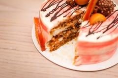 Sluit omhoog Heerlijke romige cake met chocolade, oranje plakken, pijpje kaneel op houten lijst met knipsel Royalty-vrije Stock Fotografie