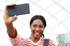 Sluit omhoog het gelukkige jonge Afrikaanse Amerikaanse vrouw nemen selfie en het lachen royalty-vrije stock fotografie