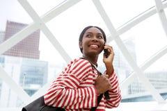 Sluit omhoog het gelukkige jonge Afrikaanse Amerikaanse vrouw spreken op mobiele telefoon en erachter het kijken stock foto