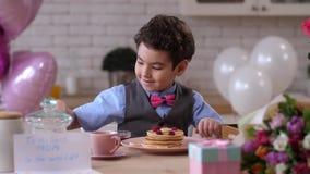 Sluit omhoog het glimlachen jong geitje verfraaiend pannekoeken voor mamma stock video