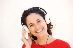 Sluit omhoog het glimlachen het jonge vrouw luisteren aan muziek met hoofdtelefoons Royalty-vrije Stock Foto