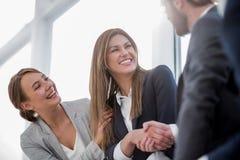 Sluit omhoog het glimlachen van het bedrijfsvrouw schudden handen met partners stock afbeelding