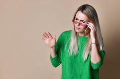 Sluit omhoog het Jonge blondevrouw Spreken aan iemand op haar Mobiele Telefoon terwijl het Onderzoeken van de Afstand met Gelukki stock foto