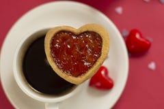 Sluit omhoog het koekje van de hartvorm met aardbeijam Kop van koffie, ochtenddrank Rode achtergrond met exemplaarruimte stock fotografie