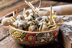 Sluit omhoog Het koken van een traditionele Pasen-cake Geschilderde kleikom met kwartelseieren in een droog stro Bruine houten ac royalty-vrije stock foto's