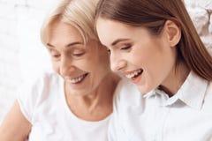 Sluit omhoog Het meisje verzorgt thuis bejaarde Zij gebruiken laptop Zij zijn gelukkig royalty-vrije stock foto
