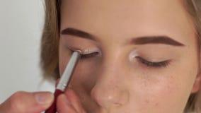 Sluit omhoog het model van de gezichtsmake-up terwijl het toepassen van ogenschaduw met kosmetische borstel in schoonheidssalon V stock footage