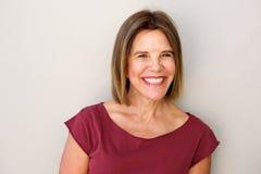 Sluit omhoog het mooie middenleeftijdsvrouw glimlachen tegen witte muur royalty-vrije stock afbeeldingen