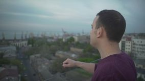 Sluit omhoog het oogmening van de panoramavogel over de donkere haired mens die zich op rand van dakdagdromen bevinden weg zeegez stock footage