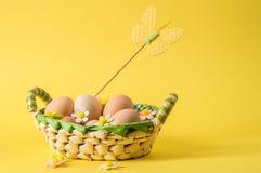 Sluit omhoog Het stilleven van Pasen Rustieke eieren in een rieten mand Het decor van de gevoelde bloemen en de vlinder van paste royalty-vrije stock foto's