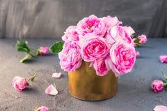 Sluit omhoog het tedere roze boeket van theerozen in uitstekende gouden pot op de donkere achtergrond Prentbriefkaarspot omhoog D Stock Foto