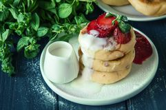 Sluit omhoog Het traditionele rustieke ontbijt maakte vers kaaspannekoeken, goot met room en verfraaide met aardbeien exemplaar royalty-vrije stock foto's
