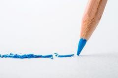 Sluit omhoog hoofd van blauw kleurenpotlood op wit tekeningsdocument, Cr stock foto
