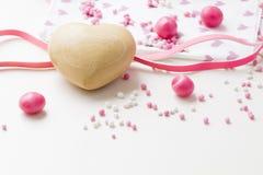 Sluit omhoog houten hart met roze en het wit bestrooit, suikergoed stock afbeeldingen