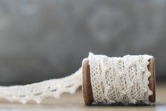 Sluit omhoog houten spoel met wit kant Ruimte voor tekst stock foto