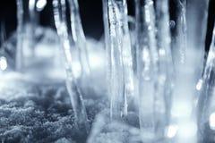 Sluit omhoog ijskegels die zich in sneeuw bij donkere nacht bevinden Royalty-vrije Stock Fotografie