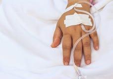 Sluit omhoog intraveneuze (iv) vastgestelde zoute druppel op kinderenhand bij pe stock foto's