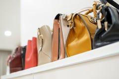 Sluit omhoog inzameling van vrouwen vrouwelijke handtassen, die zich op een rij op plank bevinden royalty-vrije stock fotografie