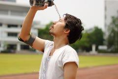 Sluit omhoog jong Aziatisch agent gietend water met waterbottle op zijn gezicht na het lopen op spoor royalty-vrije stock foto