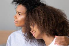 Sluit omhoog jonge Afrikaanse Amerikaanse moeder die tienerdochter koesteren royalty-vrije stock foto's