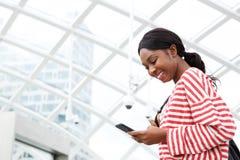 Sluit omhoog jonge Afrikaanse Amerikaanse vrouw die sms-bericht op mobiele telefoon bekijken royalty-vrije stock afbeelding