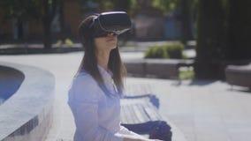 Sluit omhoog jonge vrouw die vr glazen, hoofdtelefoon, speel virtuele spelen en het letten op video's in openlucht in mooi dragen stock videobeelden