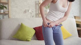 Sluit omhoog jonge vrouw probeert om op jeans te zetten wegens het bereiken van vet op haar heupen stock video