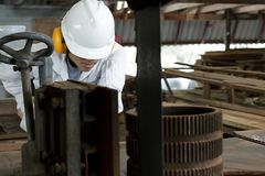 Sluit omhoog jonge werknemer in eenvormig met veiligheidsmateriaal snijdend een stuk van hout op verticale lintzaagmachine in tim Stock Afbeelding