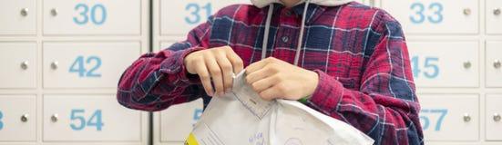 Sluit omhoog jongere snel unpackage de ontvangen levering in postkantoor, postdozen op achtergrond F stock foto