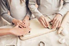 Sluit omhoog kinderen met moeder in keuken De familie maakt koekjes uit deeg stock foto's