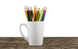 Sluit omhoog kleurenpotloden in witte ceramische kop Stock Foto