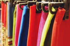Sluit omhoog Kleurrijke kledingskleding op hangerrek stock afbeelding