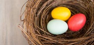 Sluit omhoog, Kleurrijke paaseieren in nest op houten achtergrond vlak Royalty-vrije Stock Fotografie