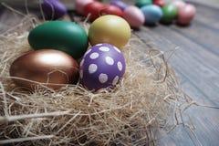 Sluit omhoog kleurrijke paaseieren in nest op houten lijst stock fotografie