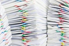 Sluit omhoog kleurrijke paperclip met stapel van rapport Stock Afbeeldingen