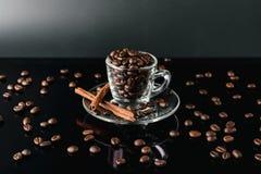Sluit omhoog koffieboon op de donkere achtergrond van het kopglas Stock Afbeelding