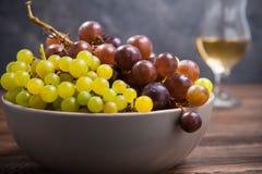 Sluit omhoog kom van diverse druiven: rode, witte en zwarte bessen op de donkere houten lijst met glas witte wijn op de achtergro Stock Foto's