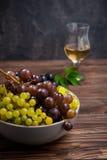 Sluit omhoog kom van diverse druiven: rode, witte en zwarte bessen op de donkere houten lijst met glas witte wijn op de achtergro Stock Foto