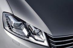 Sluit omhoog koplamp van grijze auto bij dag Royalty-vrije Stock Afbeelding