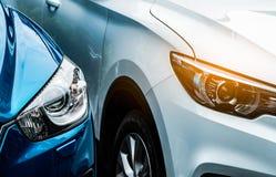 Sluit omhoog koplamplicht van blauwe en witte SUV-auto Blauwe die auto naast witte auto wordt geparkeerd De automobielindustrieco stock foto's