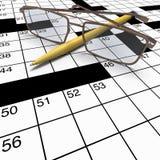 Sluit omhoog kruiswoordraadsel met pen en bril Stock Afbeelding