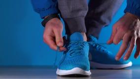 Sluit omhoog langzame motie die van benensamenstelling met schoen van de Mensen de bindende sporten van sportschoenen bij gymnast stock footage