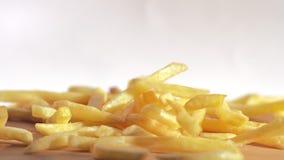 Sluit omhoog langzame motie gebraden chips die neer vanaf bovenkant aan houten lijst vallen stock video