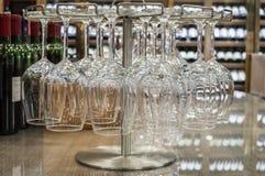 Sluit omhoog lege wijnglazen die bovenkant - neer in een wijnopslag hangen Stock Afbeeldingen