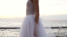 Sluit omhoog lengte van bevallige ballerina in witte lange tutu en pointe het lopen tiptoe op houten vloer ner het overzees of de stock videobeelden