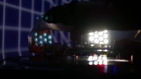 Sluit omhoog lengte van DJ die muziek mengen met een vinyl op zijn audiomixer, verandert hij het stock videobeelden